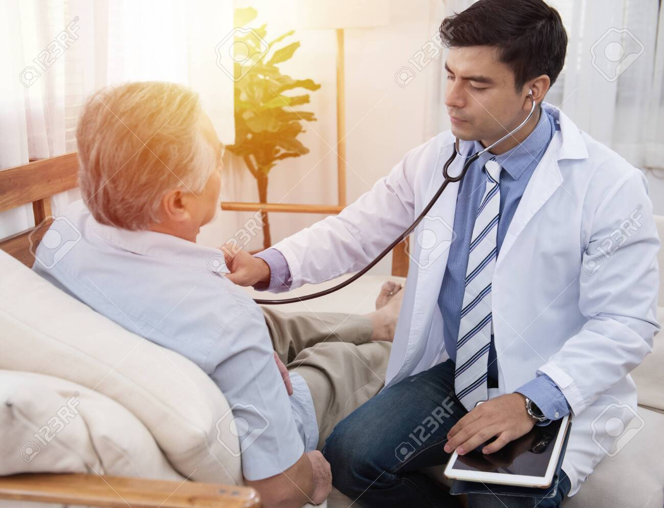 Caucasian doctor sit on chair check asian senior elderly old man heart beat lay down on sofa at home.Medicine and healthcare concept. - 144499096