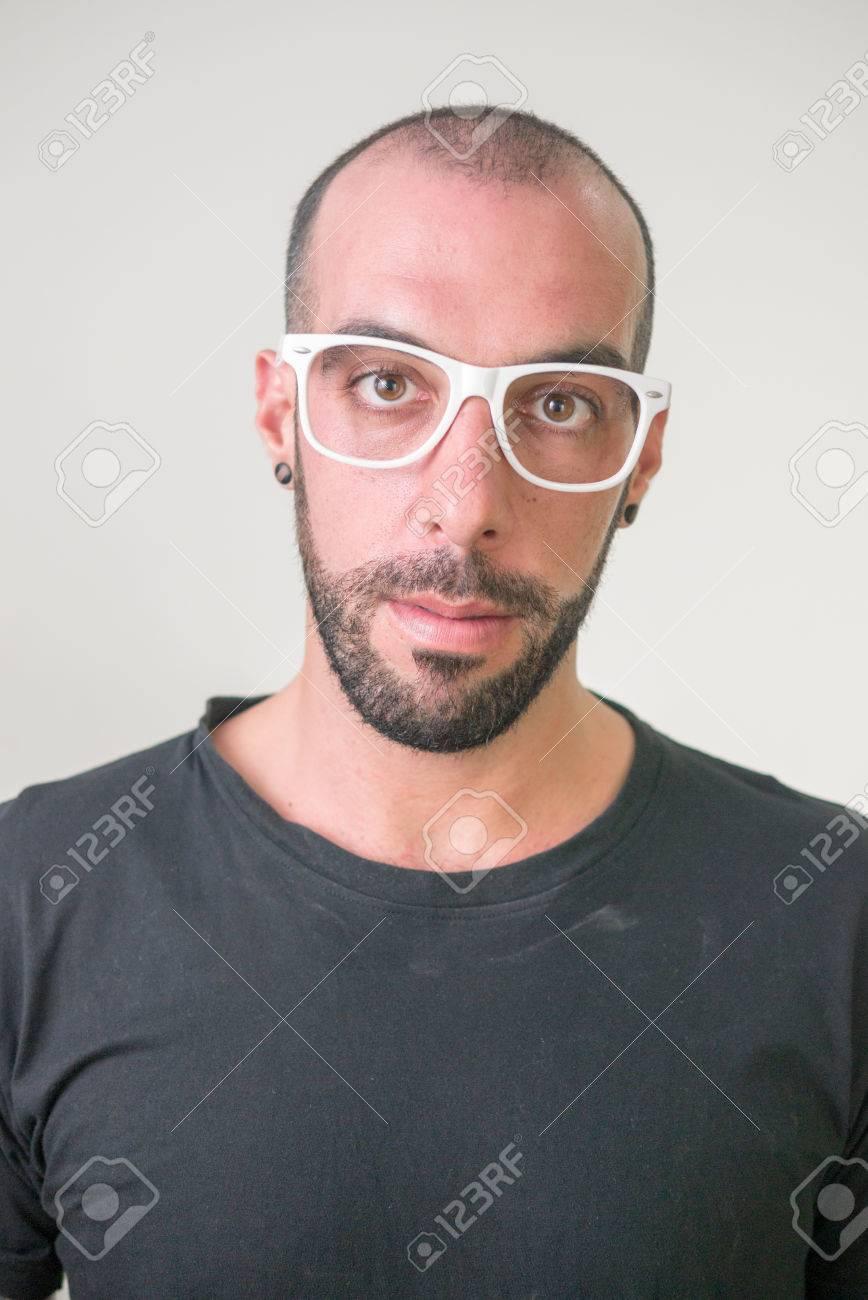 Foto de archivo , Inconformista calvo con barba que llevaba gafas blancas y negro camiseta