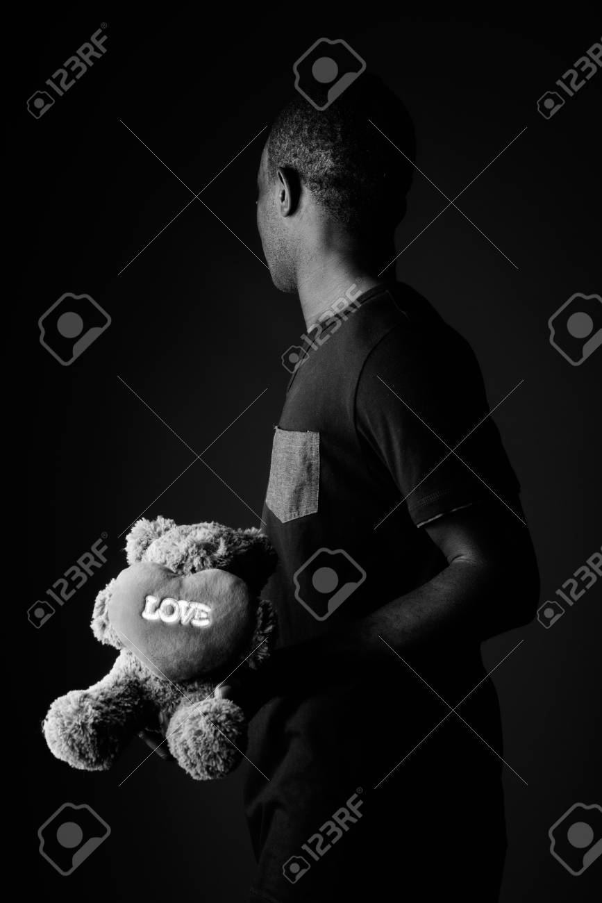 Sad young african man with teddy bear and love sign text in black and white stock