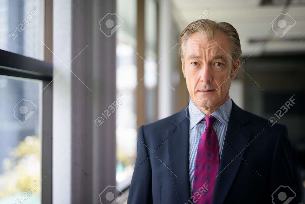 Mature handsome businessman in suit by the window at work - 145042058