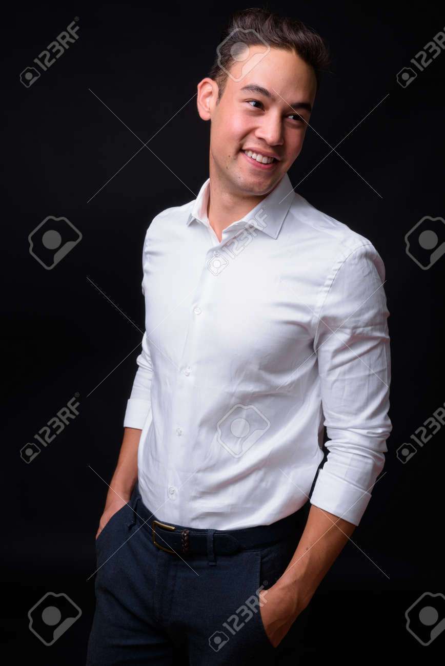 Young handsome multi ethnic businessman against black background - 145987997