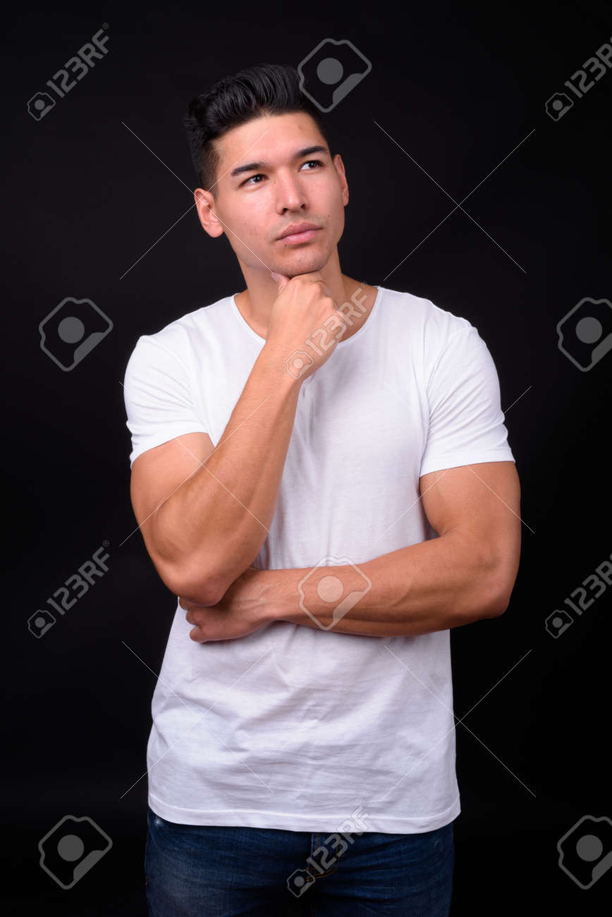 Young handsome multi ethnic man against black background - 152099855