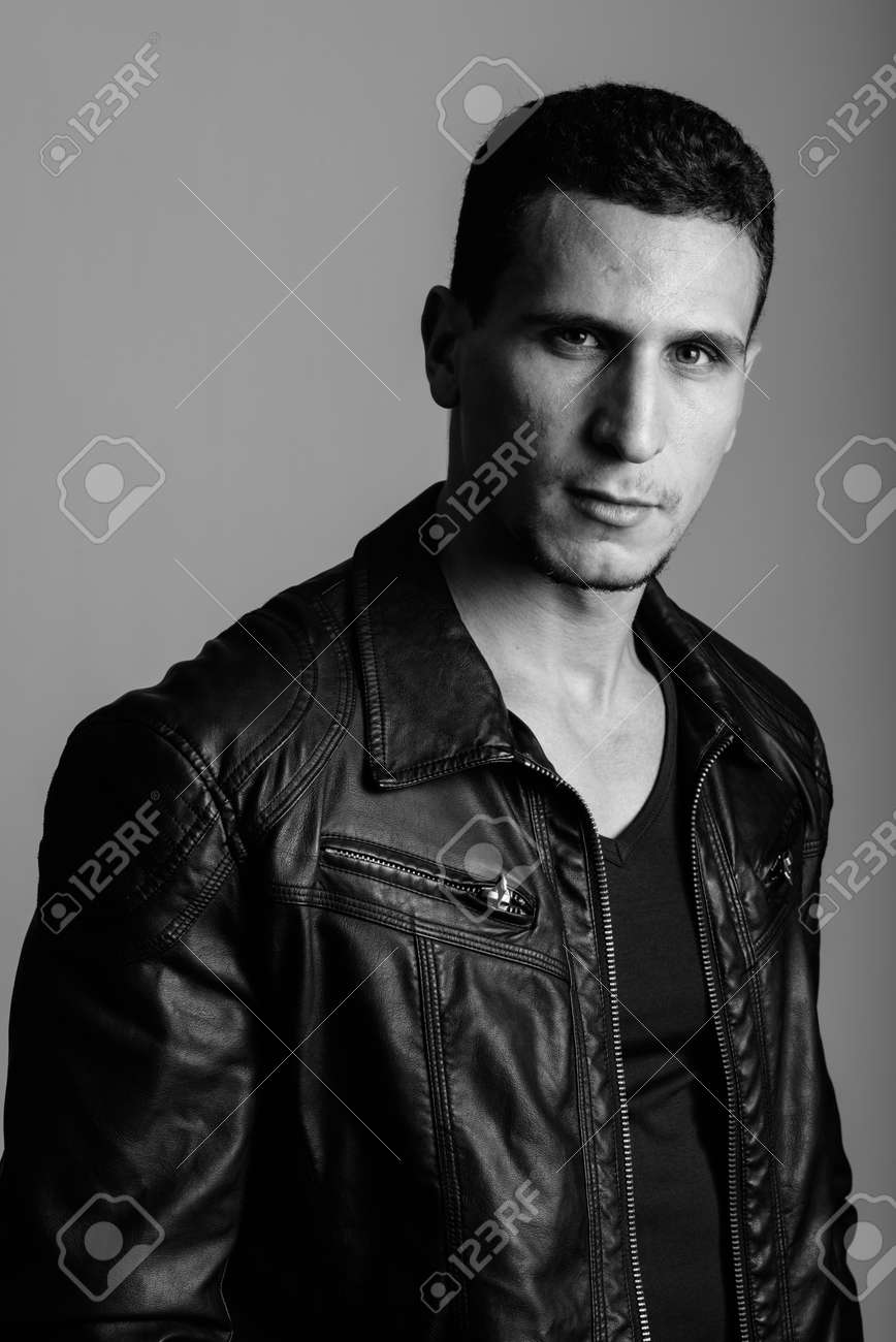 Studio shot of young muscular Persian man against gray background - 155292115