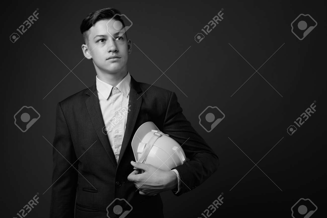 Studio shot of young handsome businessman against gray background - 155984281
