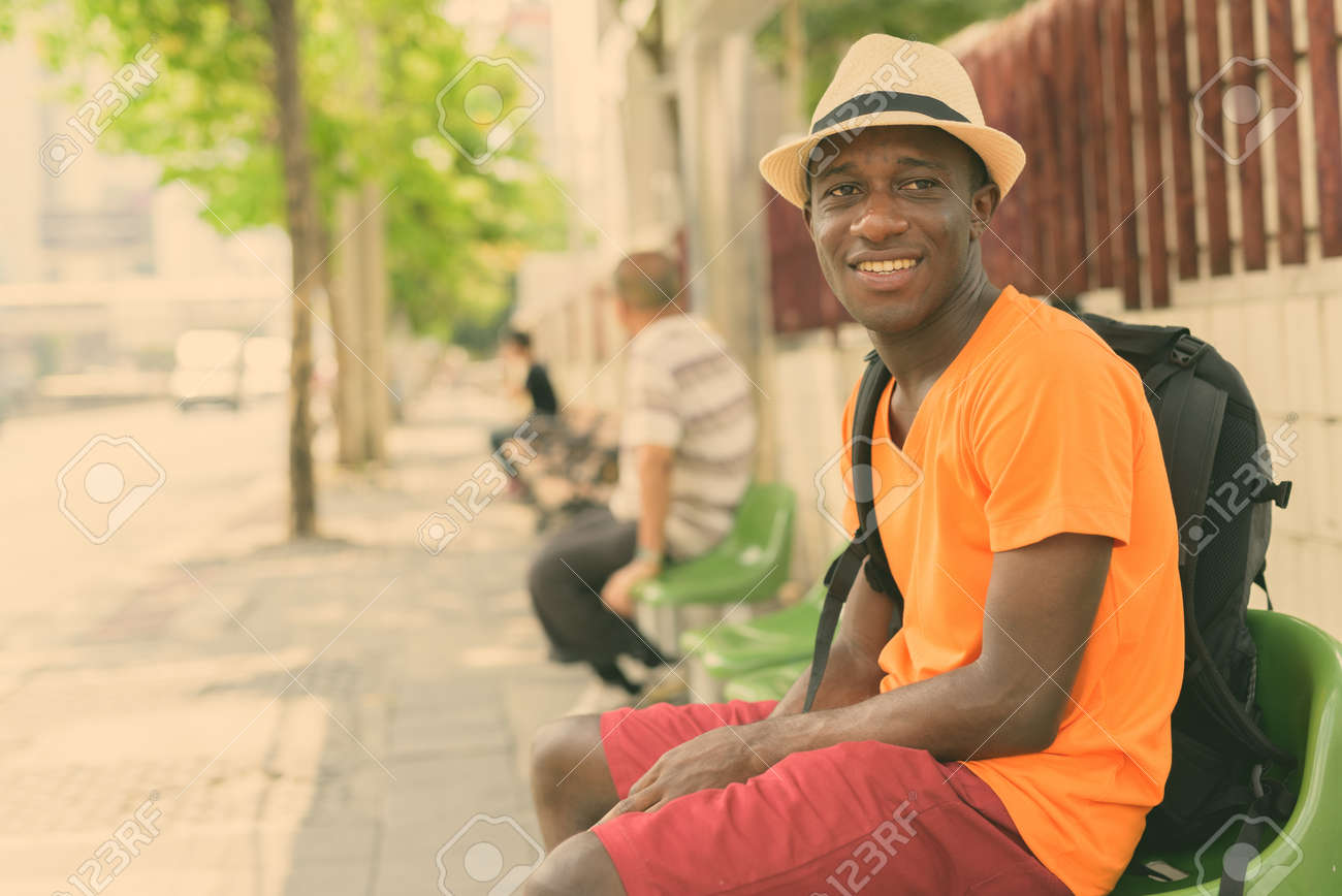 Young happy black African tourist man smiling and thinking while sitting at the bus stop in the streets of Bangkok Thailand - 157184107