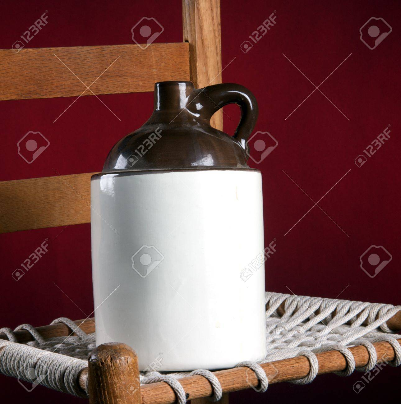 An Old Pottery Ceramic Country Jug And Rope Bottom Chair On A Red  Background In The