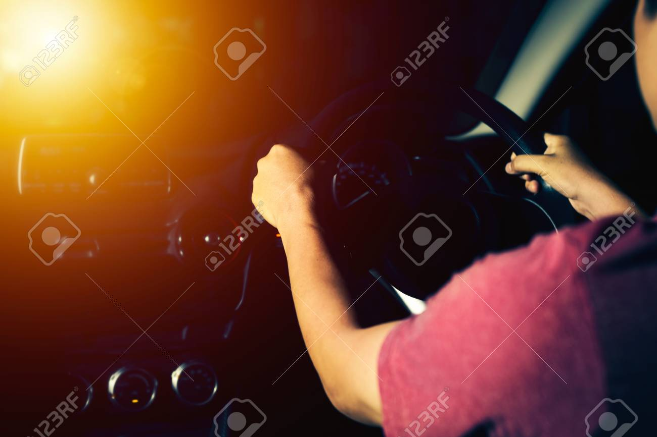 7dad6896b1 Foto de archivo - Tiro oscuro de la iluminación del hombre que conduce un  coche con efecto de la luz del sol, vintage.