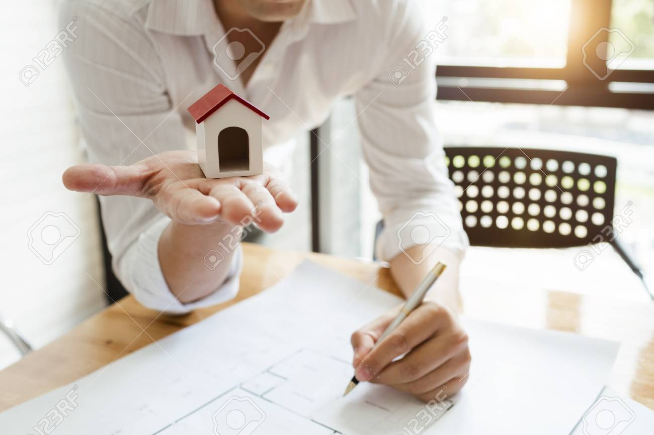 Business architect engineer drawing a house blueprint planning business architect engineer drawing a house blueprint planning to build a new home at housing estate malvernweather Choice Image