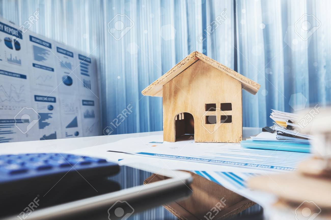 House and property for sale concept, wood house toy on office desk. - 90880852