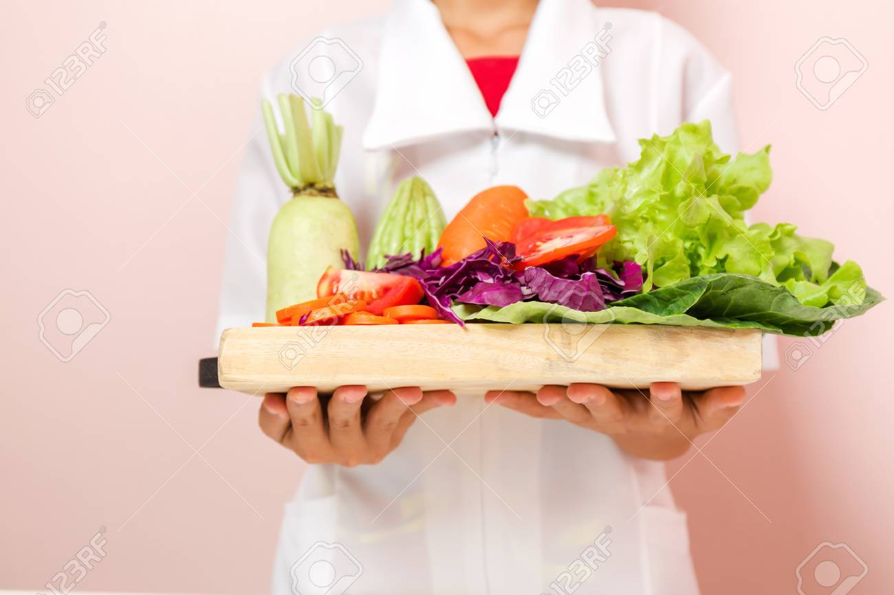 Nutritionist standing holding a tray of healthy vegetables recommended to consumers. - 93009732