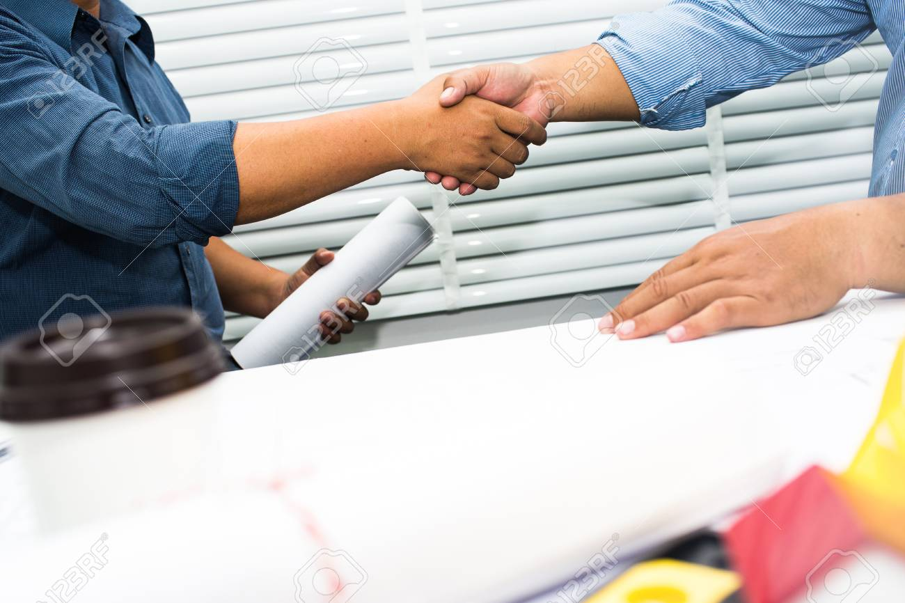 Shaking hands of engineers and contractors to sign a contract to build a house. - 93009061