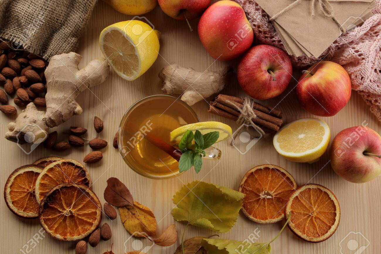Autumn composition with hot tea, fruits and yellow leaves on a natural wooden table. view from above - 149555235