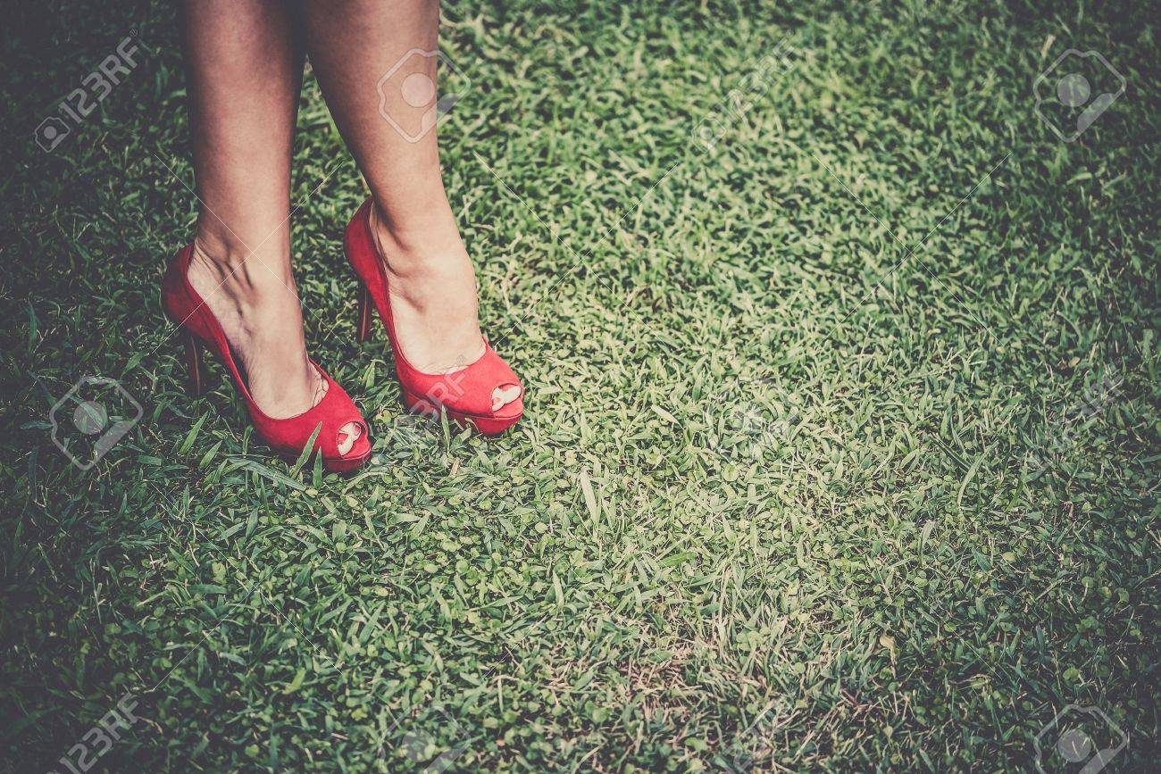 e834762eb0c Stock Photo - Woman s legs in bright red shoes with high heels crossed on  grass