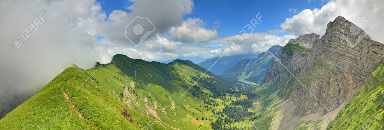 panorama of a mountain valley formed by two steep ridges with settlement and lake on the bottom in summer seen from ridge, below mountain Bockmattli Stock Photo - 8164896
