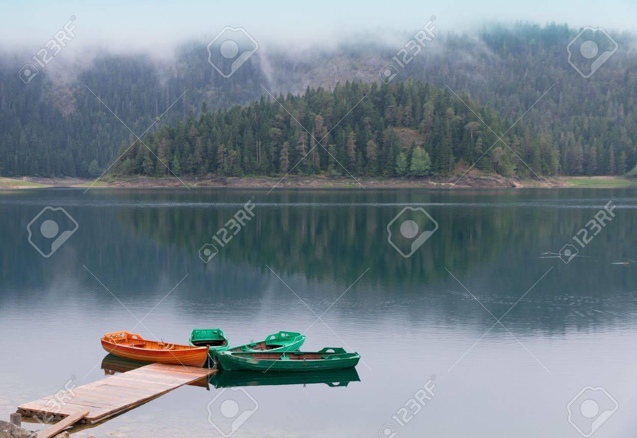 Quiet black watered  lake with boat pier, forest reflecting in UNESCO world heritage National Park Durmitor with fog and clouds,  Montenegro Stock Photo - 8946180