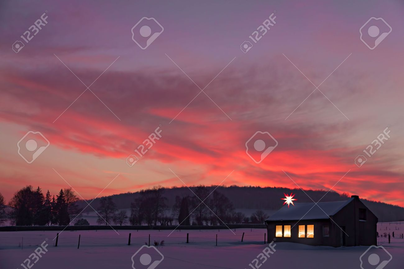 little house with decorated windows lighted in front of a winter sunset in snow Stock Photo - 10744159