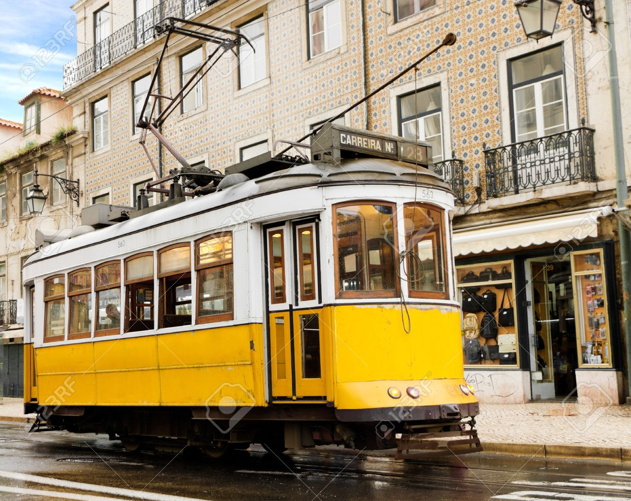 historic classic yellow tram of Lisbon built partially of wood navigating, narrow, winding streets, Portugal Stock Photo - 12200882