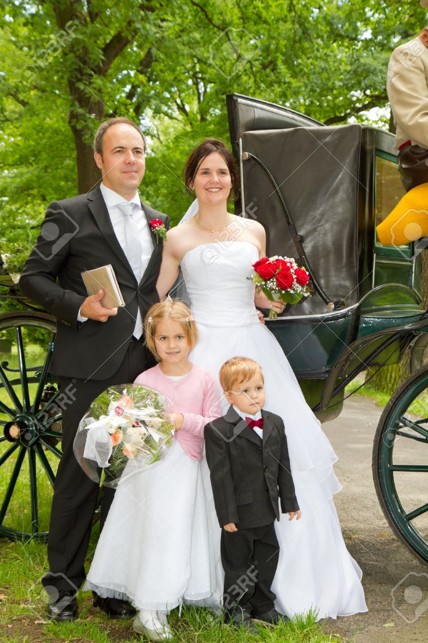 Newly Wed Couple And Children With Wedding Gown, Dark Suit And ...