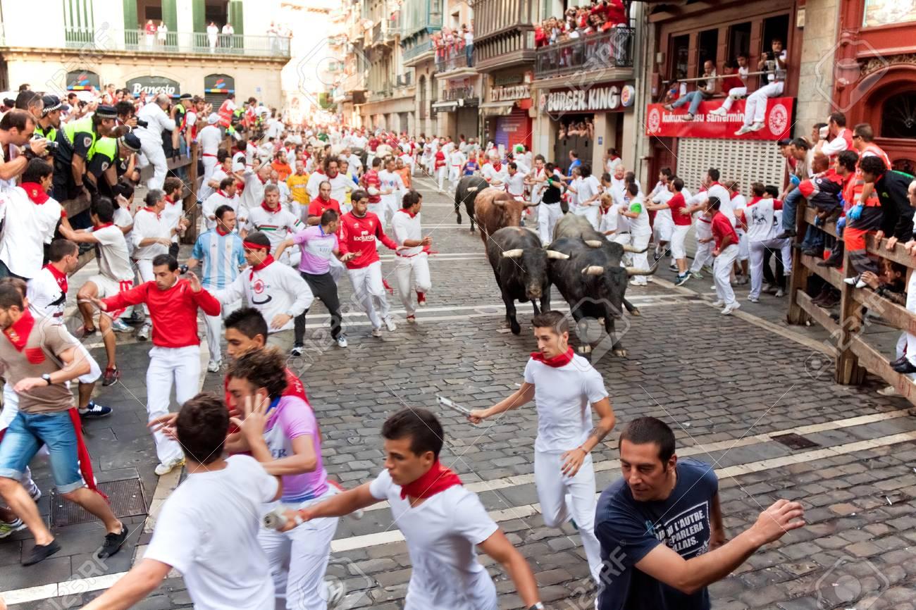 PAMPLONA, SPAIN -JULY 14: Unidentified men run from bulls in street Estafeta during San Fermin festival in Pamplona, Spain on July 14, 2013. - 23383543