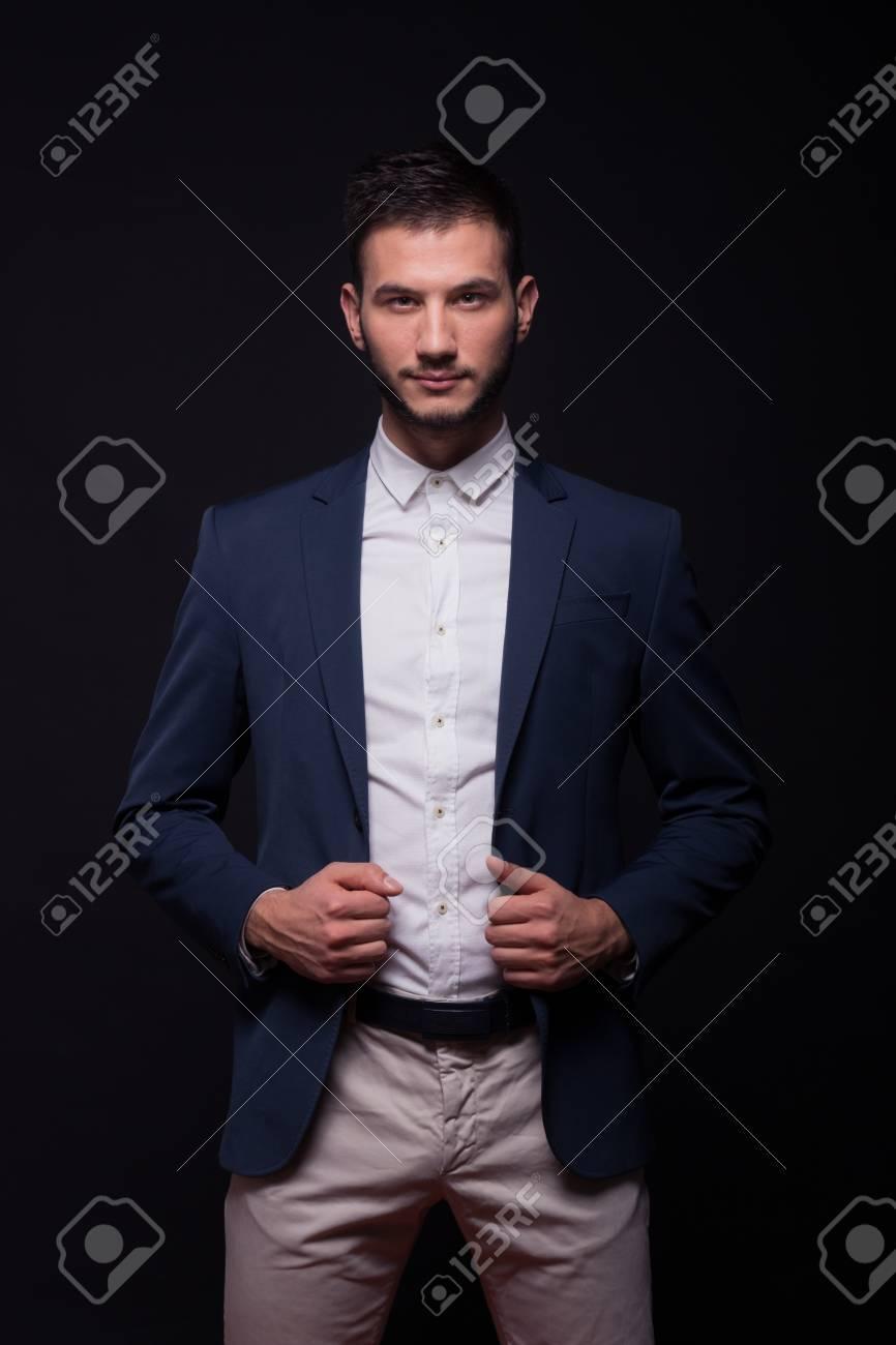 Adulto joven modelo de hombre elegante camisa pantalones de traje, la celebración de la chaqueta azul, fondo negro