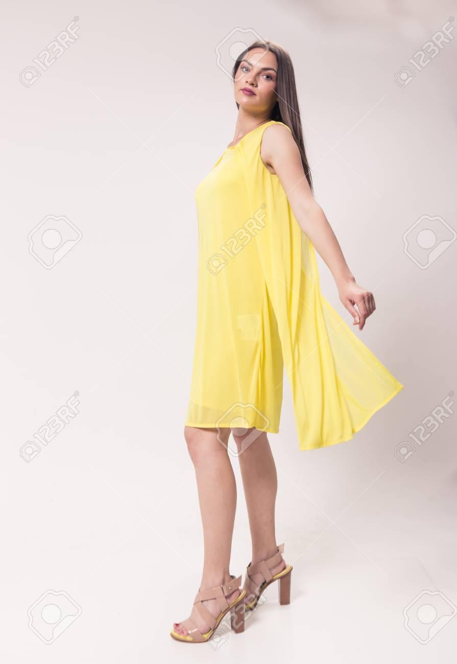 Una mujer joven de raza caucásica, estudio, fondo blanco, vestido amarillo, zapatos de tacón alto, moda, movimiento de movimiento