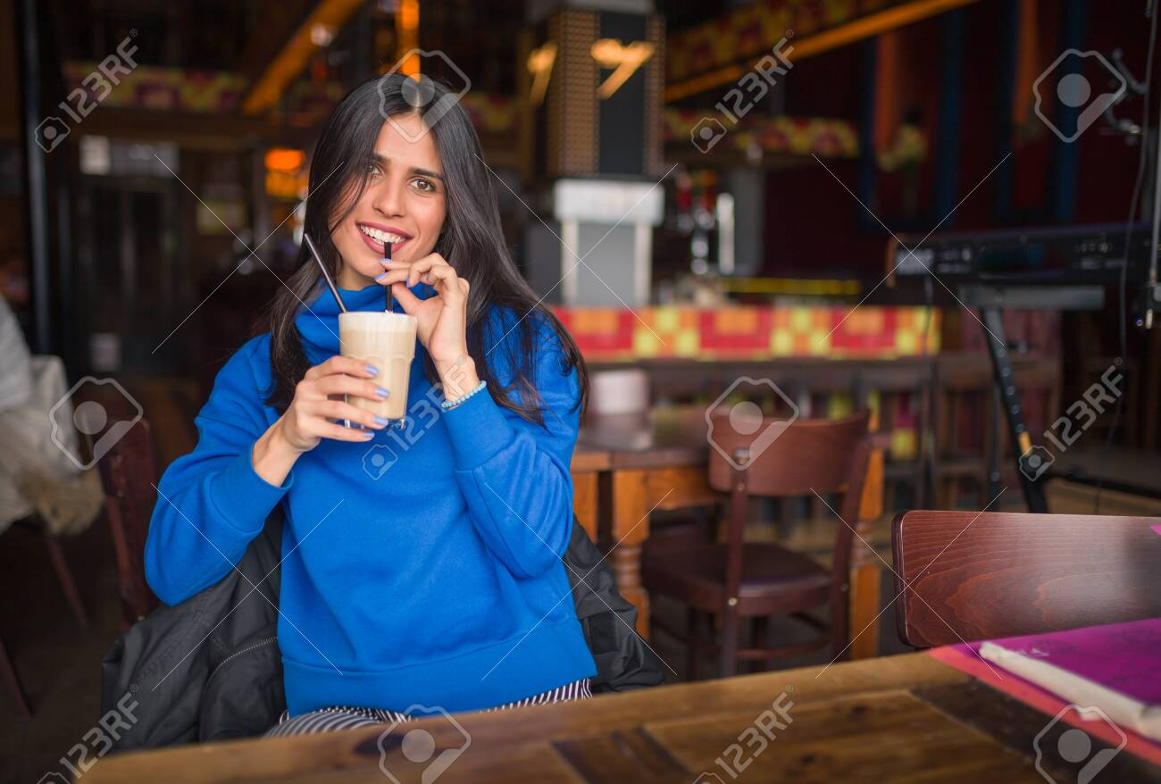 Portrait of pretty brunette in a cafe. Enjoying latte and looking at camera. - 157323267