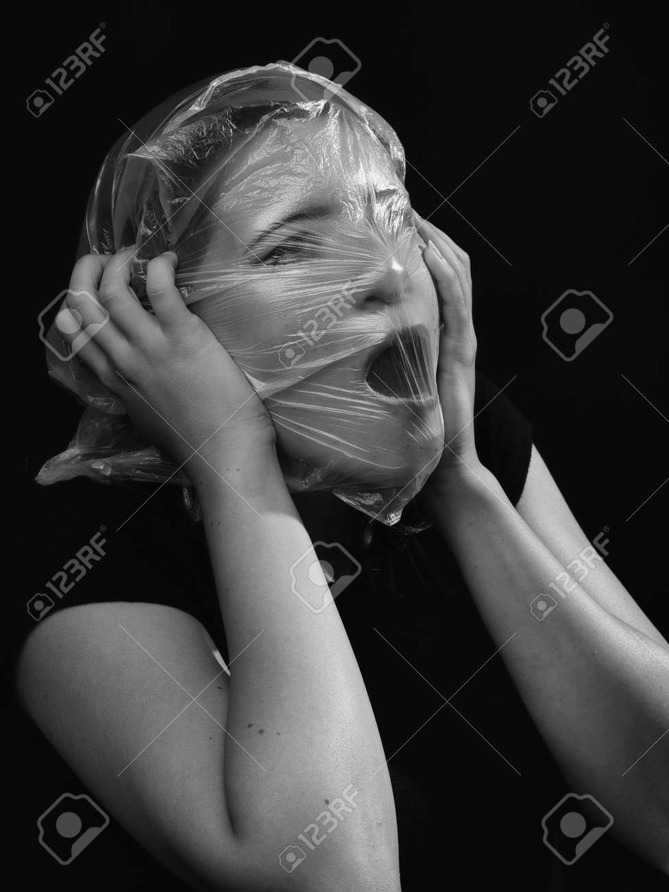 conceptual portrait, one young beautiful woman wraped in plastic sheet. Shot in studio, white background. - 164118957
