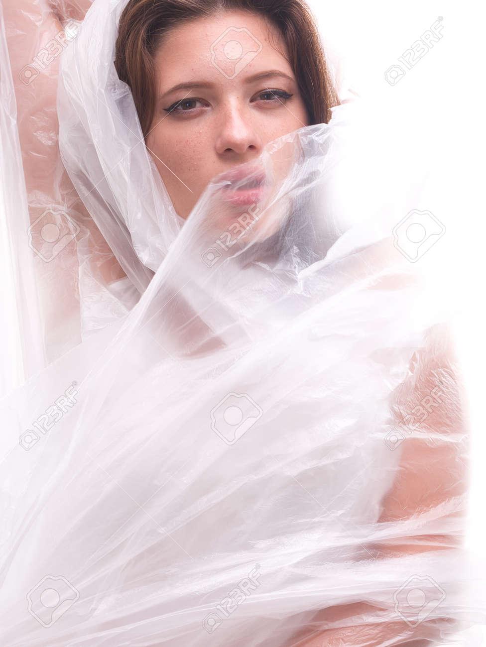 high key. Conceptual portrait with plastic sheets. One young woman strugling with plastic sheets. - 164118909
