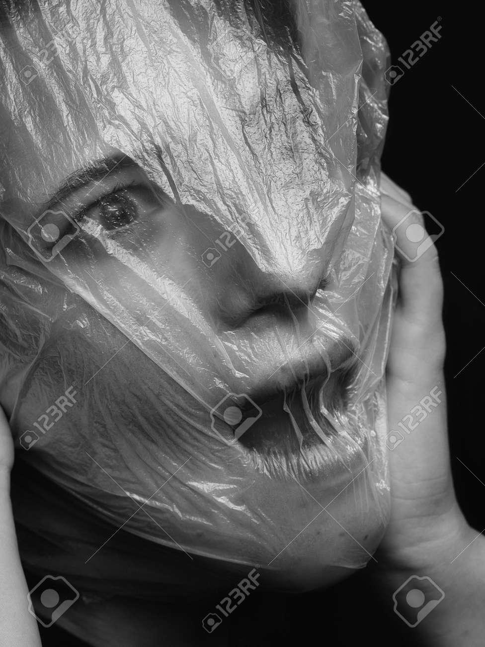 high key. Conceptual portrait with plastic sheets. One young woman strugling with plastic sheets. - 164118917
