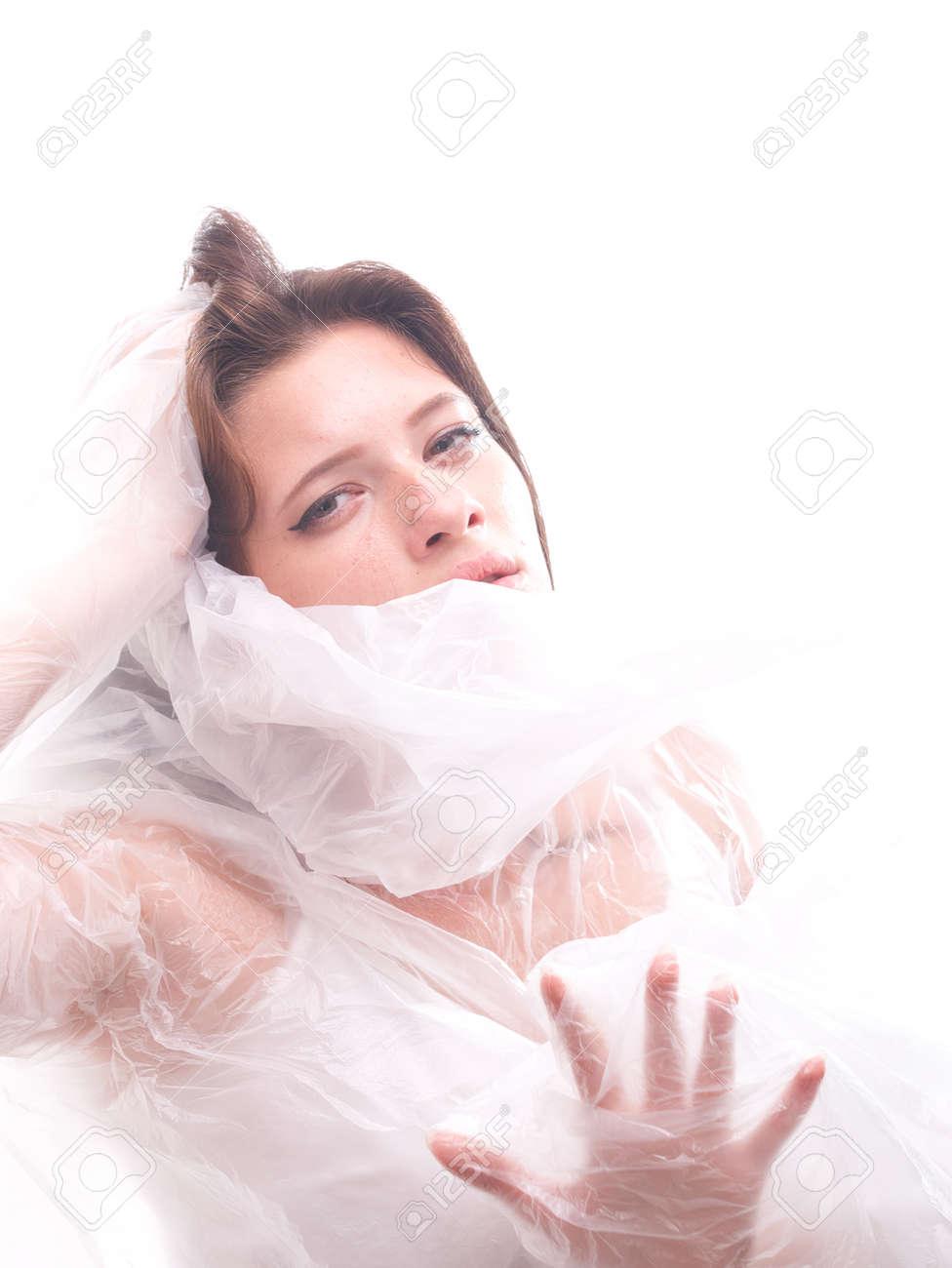 high key. Conceptual portrait with plastic sheets. One young woman strugling with plastic sheets. - 164118923