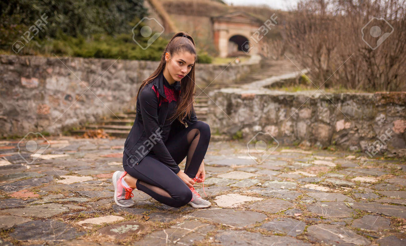 one young woman, stretching outdoors, on a winter day. - 170692594