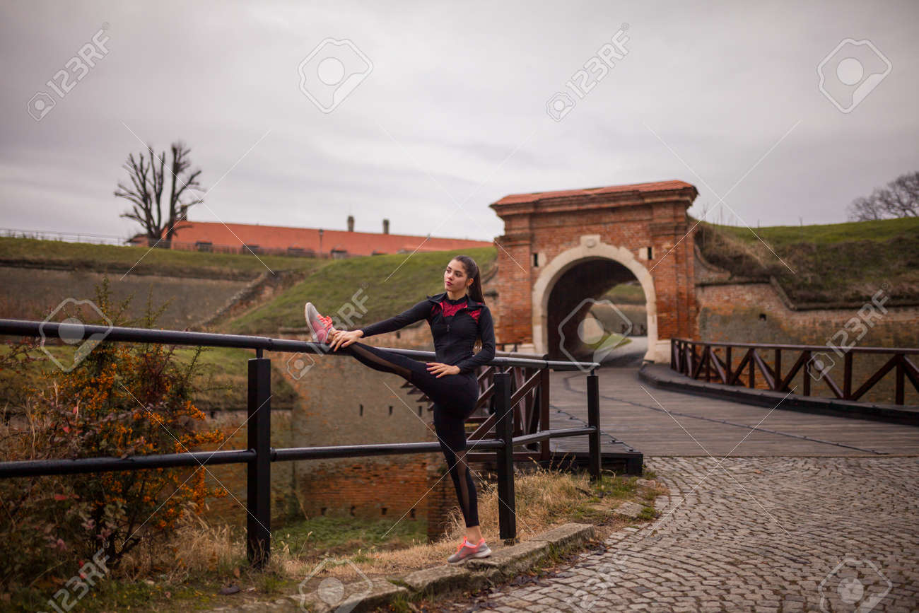one young woman, stretching outdoors, on a winter day. - 170692535