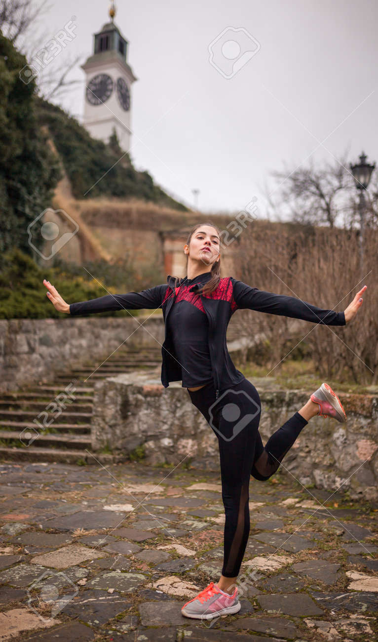 one young woman, stretching outdoors, on a winter day. - 170692545