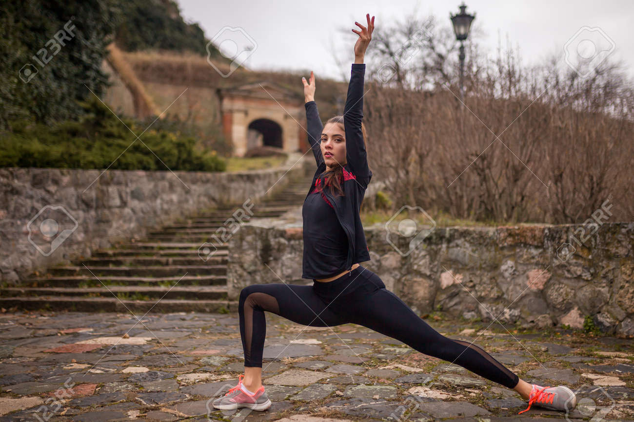 one young woman, stretching outdoors, on a winter day. - 170692546