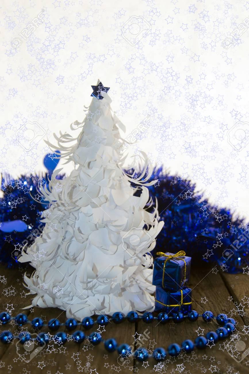 Foto Alberi Di Natale Bianchi albero di natale bianco origami con stella blu e decorazioni blu su una  base di legno