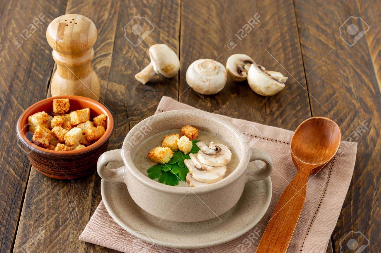 Mushroom cream soup with champignons, croutons and fresh herbs on rustic white wooden table. - 165710783