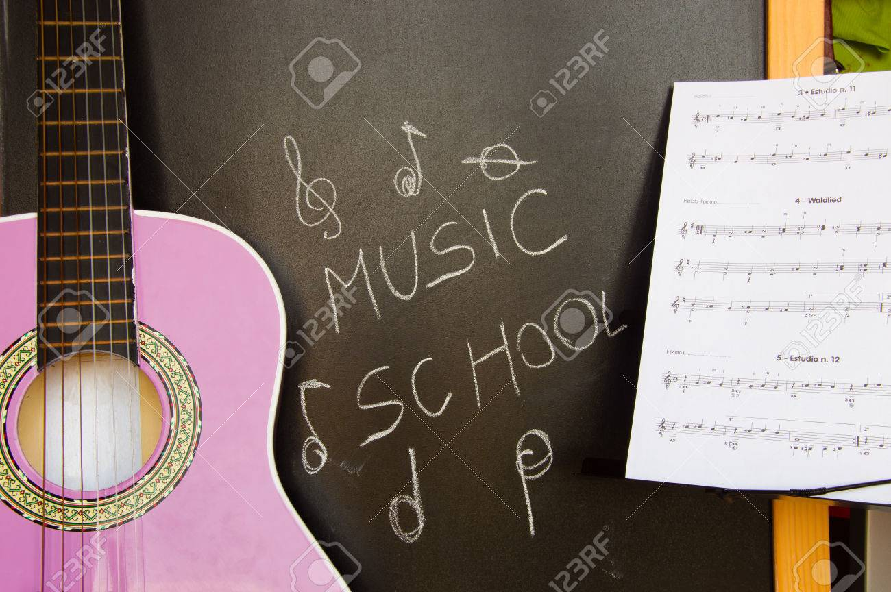 Music school for children with purple guitar closeup on blackboard background and music sheets Stock Photo - 48325009
