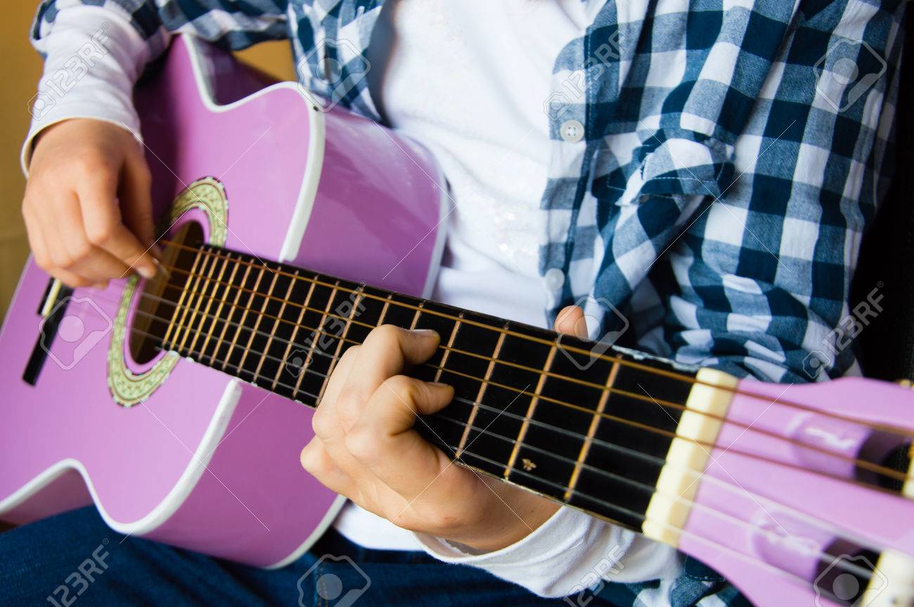 Music school for children with purple guitar closeup and child playing Stock Photo - 48325010
