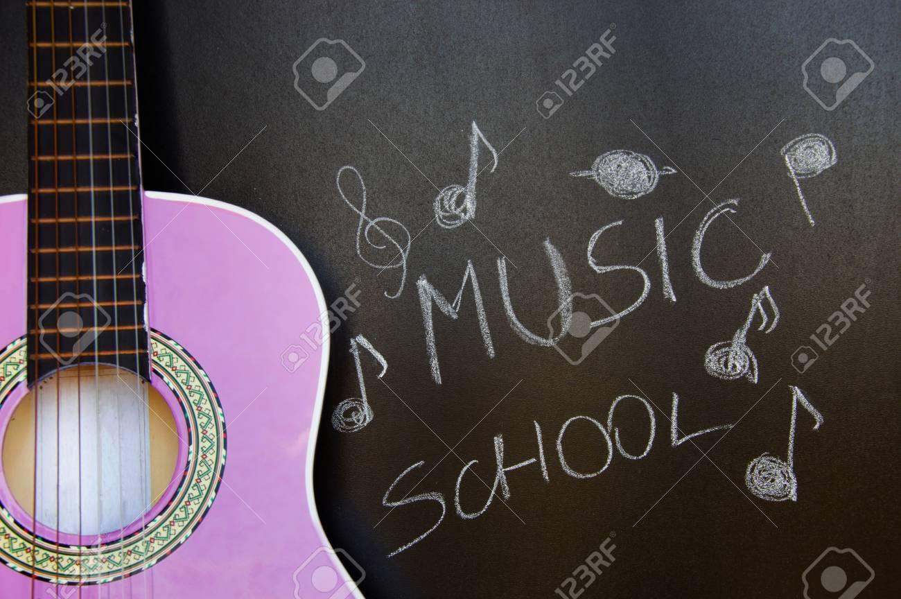 Music school for children with purple guitar closeup on blackboard background Stock Photo - 48325016