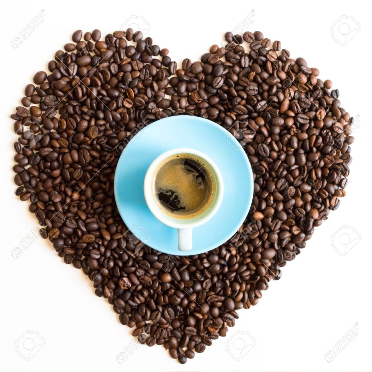 Heart of coffee beans with azure blue cup isolated on white background Stock Photo - 80156032