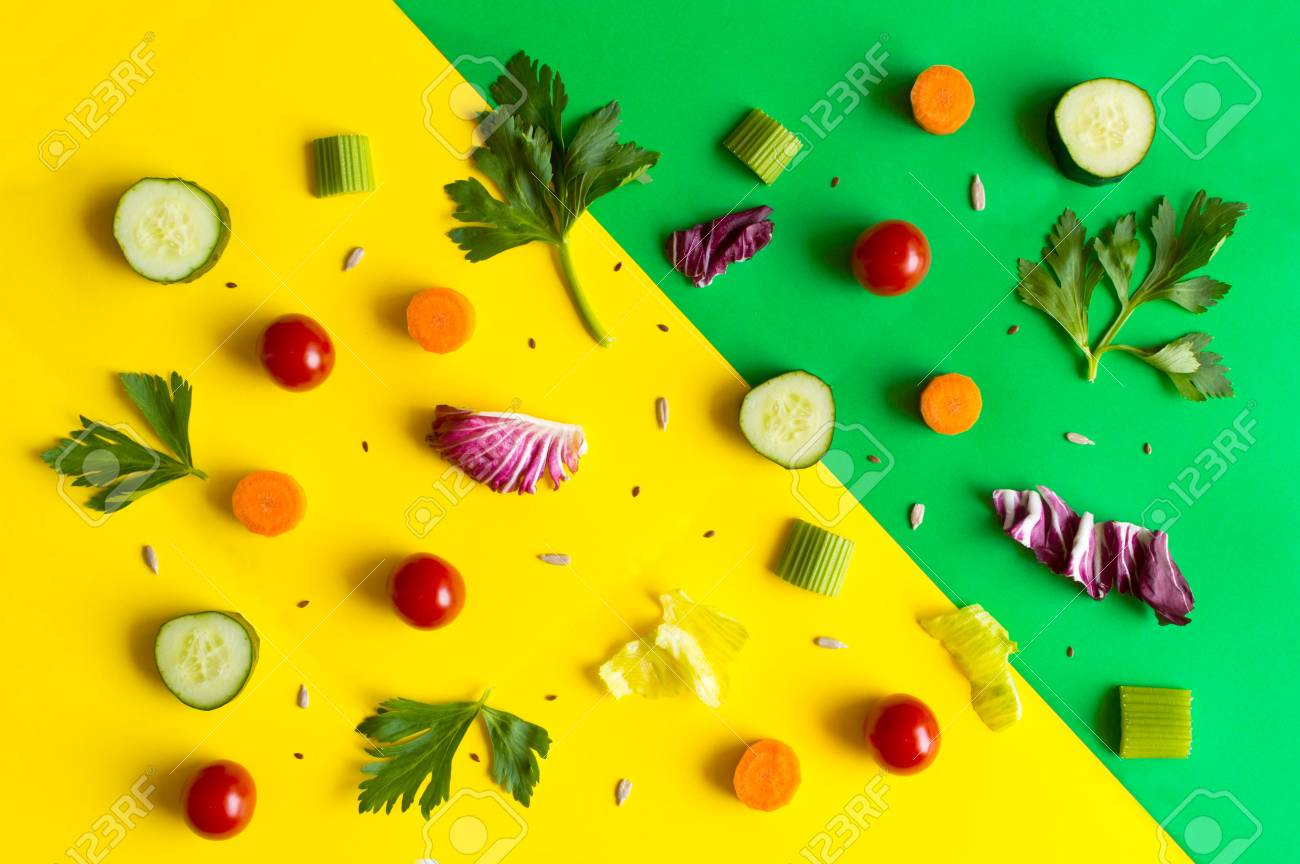 Eating pattern with raw ingredients of salad, lettuce leaves, cucumbers, red tomatoes, carrots, celery on colorful green and yellow background Stock Photo - 91977891