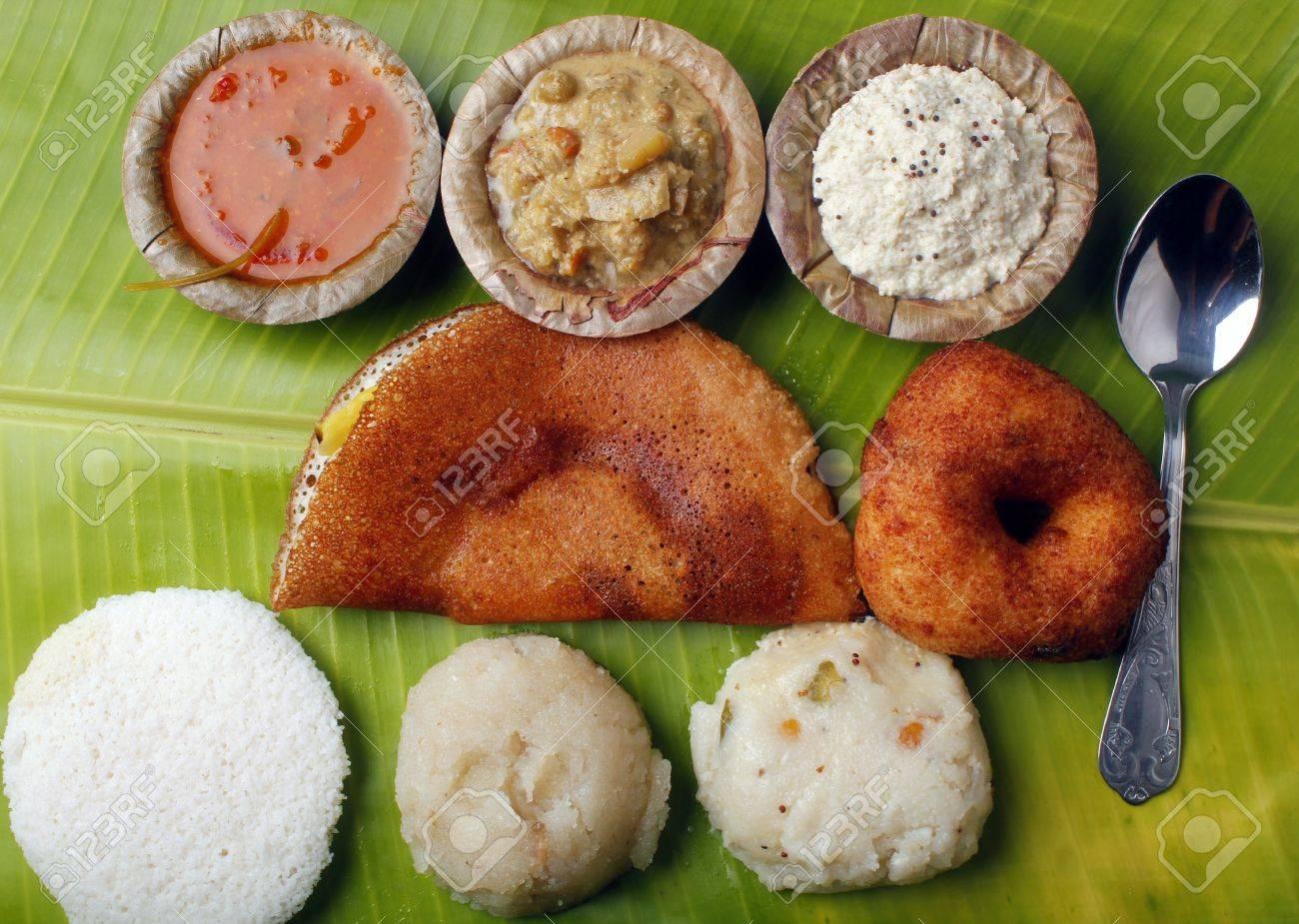 Masala dosa, idly, vada, chutney, upma, curry and sambar on a banana leaf Stock Photo - 10227229