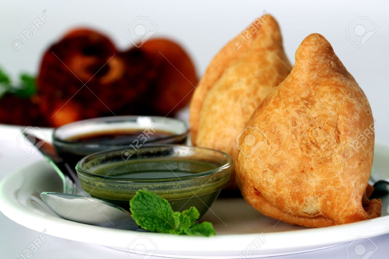 Popular indian, asian and african deep fried snack called samosa with spicy chutney and mint Stock Photo - 12922427