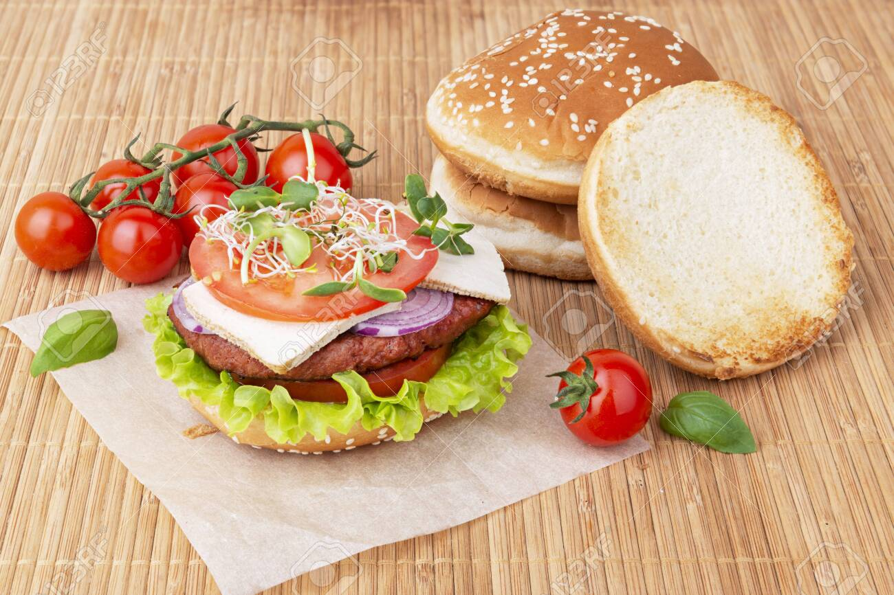 Home cooked vegan burger with soy cutlet, micro greens, tomatoes and crunchy bun - 143110664