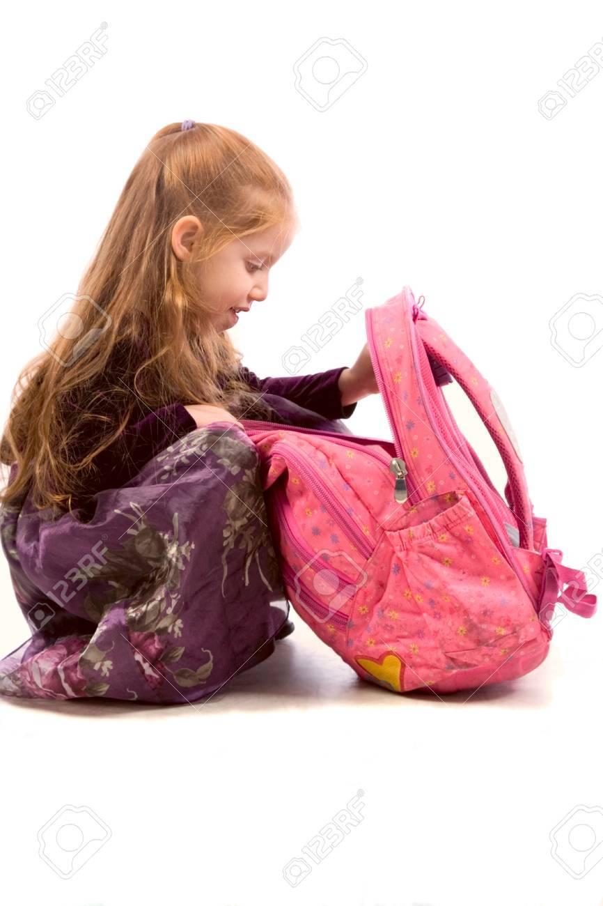 Very young schoolgirl looking into her pink backpack Stock Photo - 834030