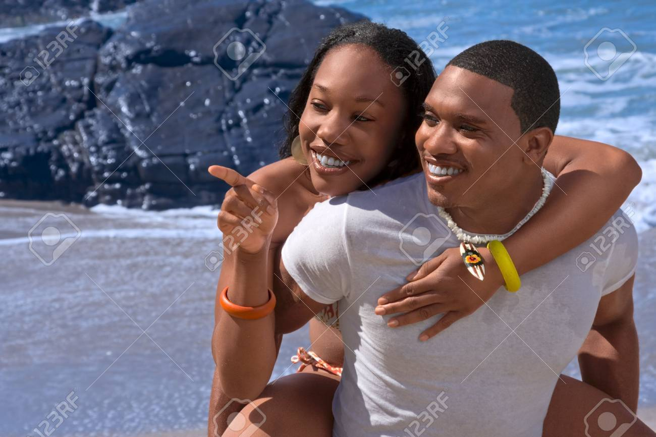 Attractive African-American young couple having fun on beach Stock Photo - 1789871