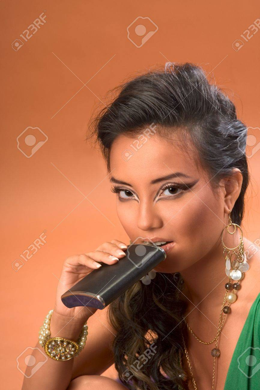 Young woman drinking alcohol from hip flask Stock Photo - 2349370