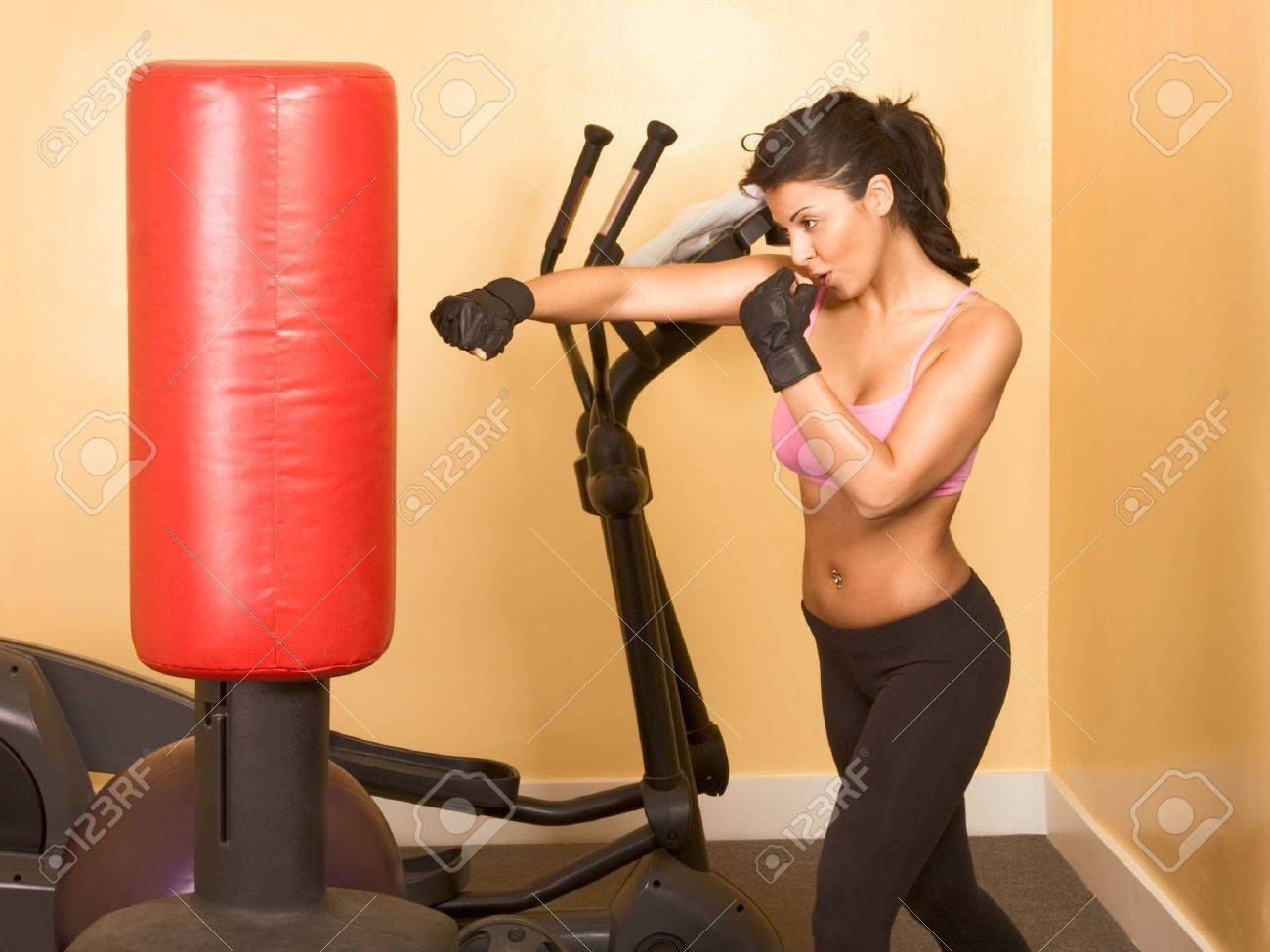 Attractive woman kickboxing using red punching bag - 3249043