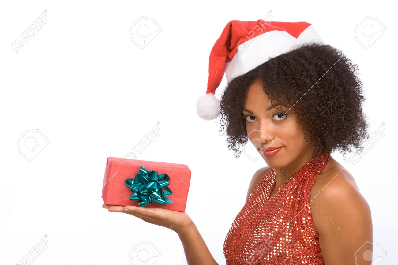 Dark skinned middle aged woman in sexy Mrs. Santa Claus outfit holding on palm of her hand small gift box wrapped in red paper and decorated by green bow Stock Photo - 3832095
