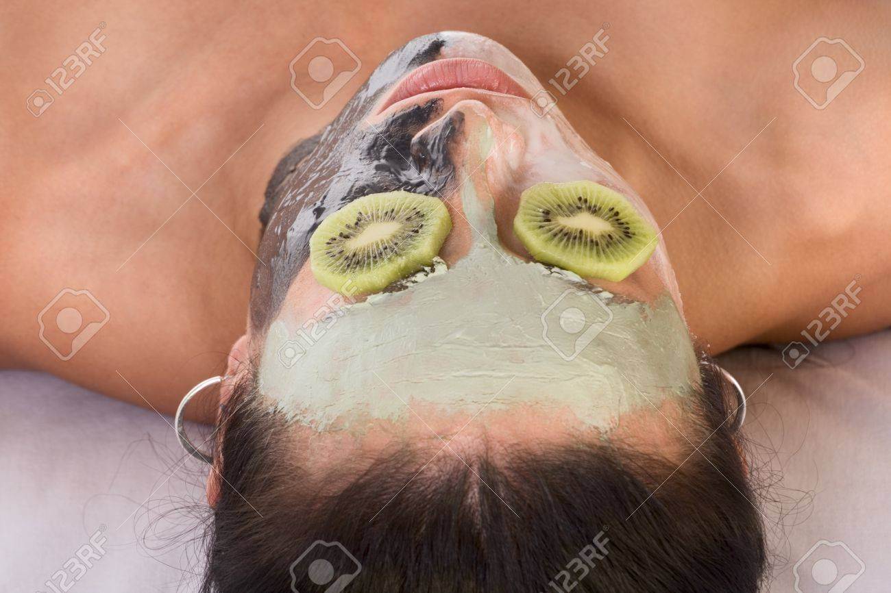 Woman lying down on her back in spa, with special facial mask applied on her face. The mask consist of three colors, each cover different part and eyes are covered by slice of kiwi Stock Photo - 3944428